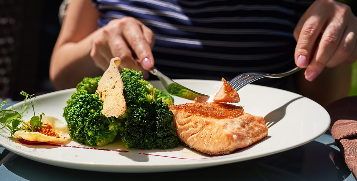 A person enjoying a salmon dinner.