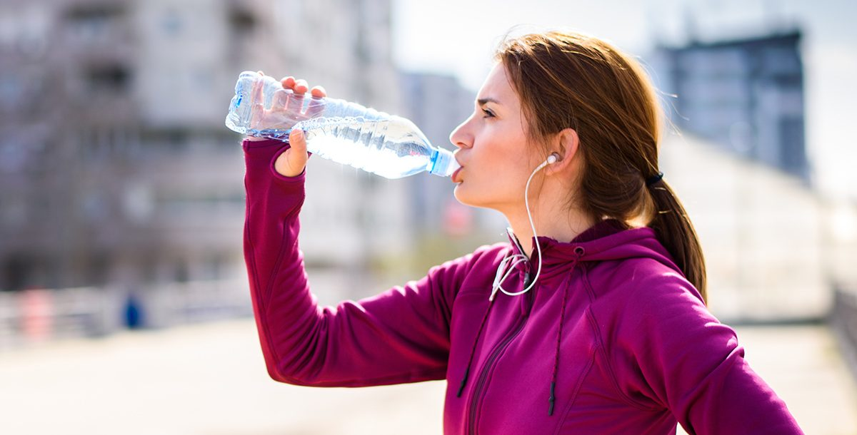 A woman drinking water before a run.