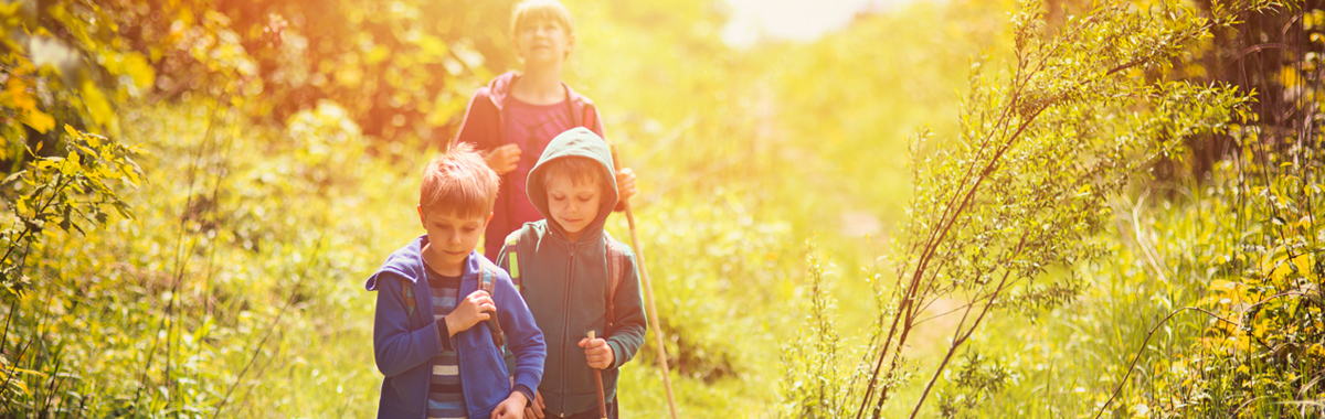 children hiking with an adult - ways to stay active outdoors