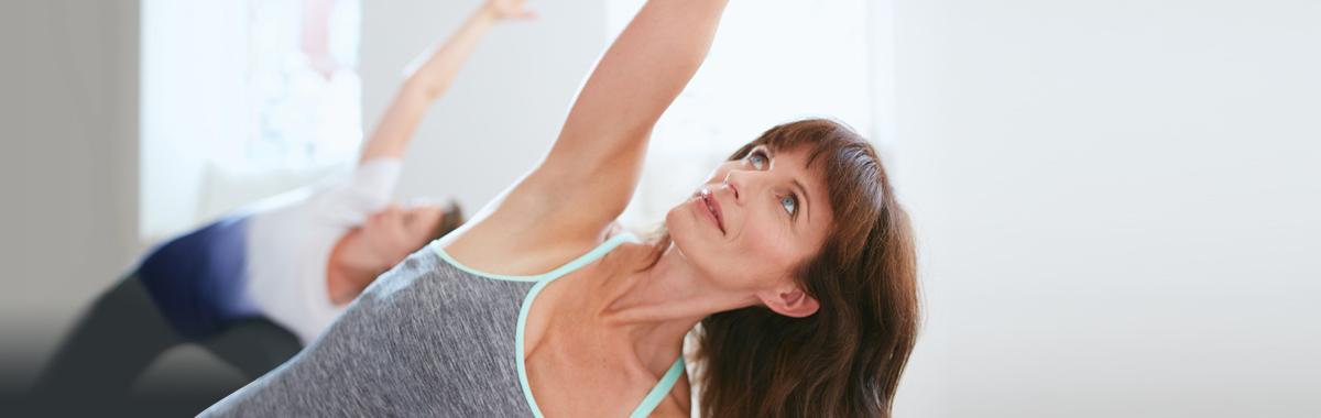 woman performing half moon pose in yoga
