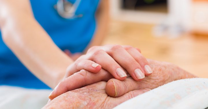 nurse holding a patients hand - national nurses week mercy health