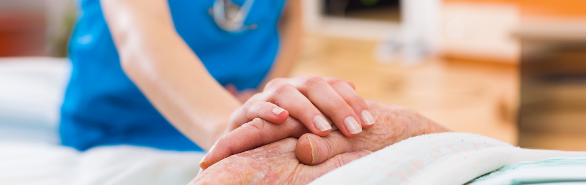 nurse holding a patients hand - national nurses week mercy health