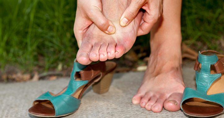 woman massages her foot after taking off high heel-ed shoe _ how to avoid common foot problems