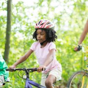 african-american family bike riding together - bike safety tips from mercy health