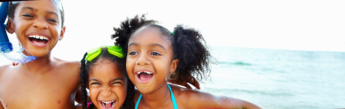 three children playing in the ocean - preventing skin cancer