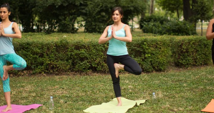 three women performing tree pose in outdoor yoga class