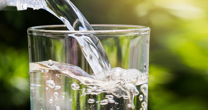 water pours into a glass _ summer hydration guide