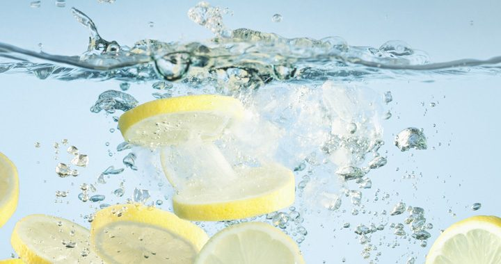 slices of lemon splash into fresh water _ benefits of drinking lemon water