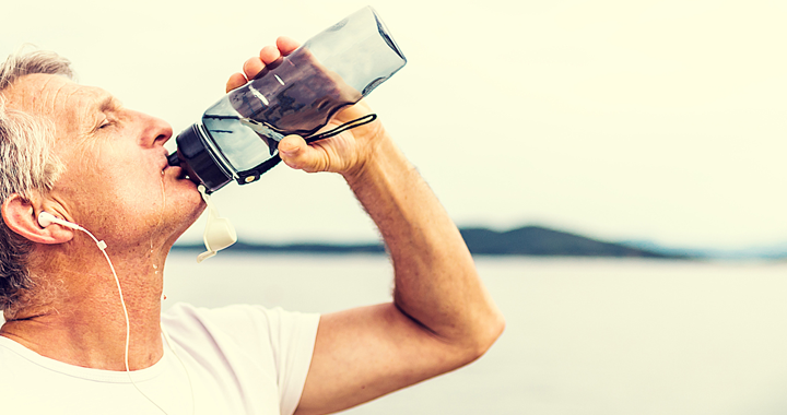 man drinks from water bottle on a beach _ how to protect your heart from the heat