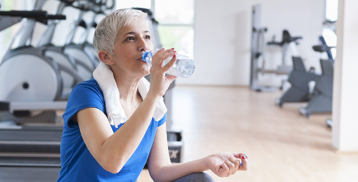 A woman drinking water during her workout.