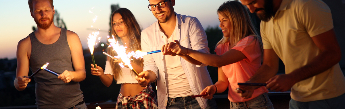 men and women light sparklers on a beach _ fireworks safety tips