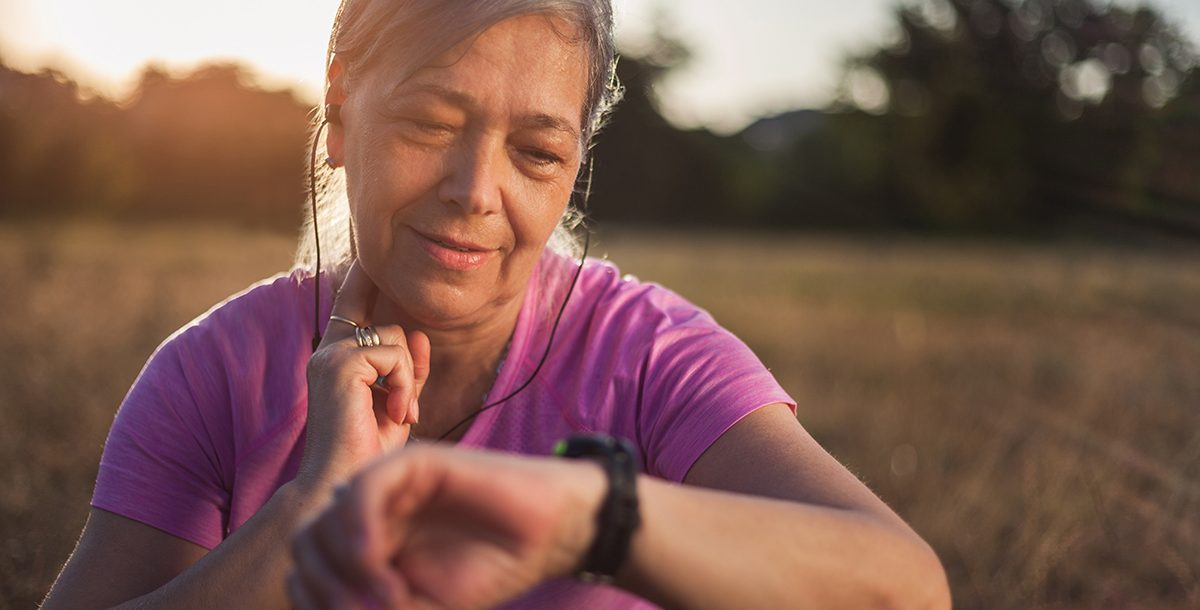 A woman checking her pulse while on a walk.