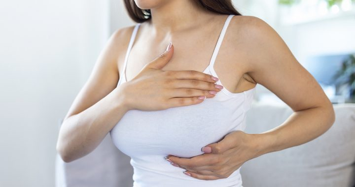 A woman performing a breast self-exam.