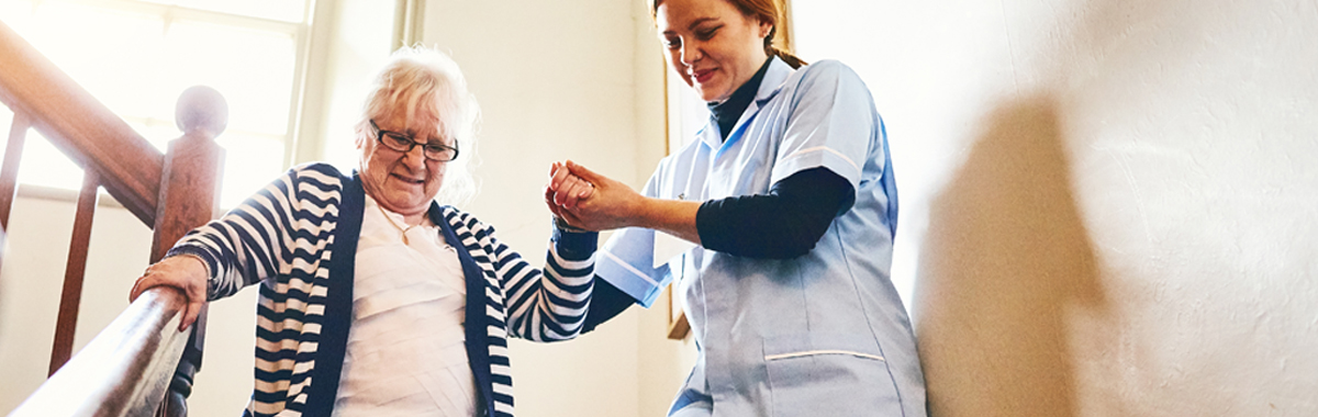 female health care worker helping female patient down stairs after joint replacement