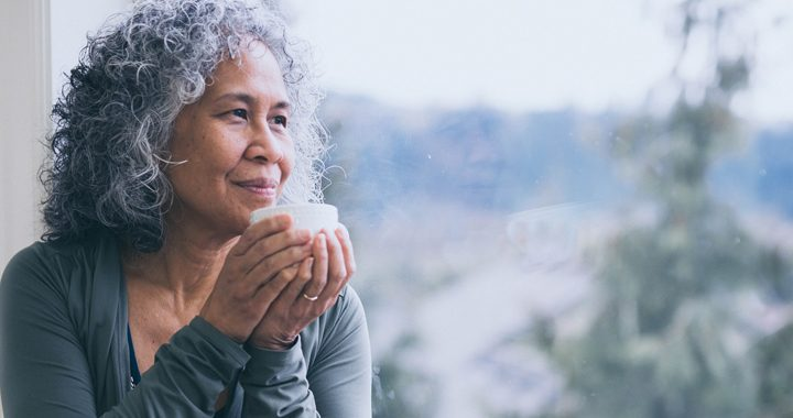 woman practicing mindfulness while holding a white mug looking out the window