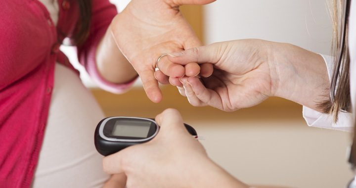 close-up of healthcare worker using blood glucose meter to test pregnant woman's blood sugar - gestational diabetes