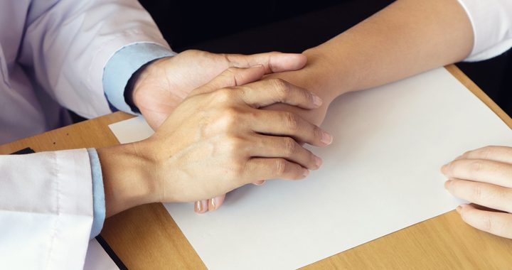 Health care provider holding a patient's hand on wooden table that has a paper on it