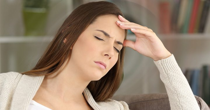 Young woman with eyes closed holding head with one hand - vertigo