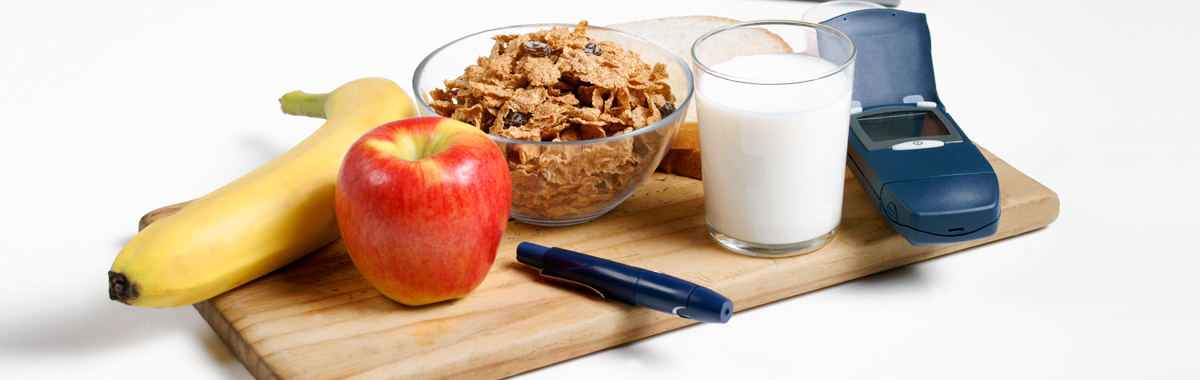 Wooden cutting board containing apple, banana, bowl of cereal, milk, bread, and blood glucose meter for diabetes