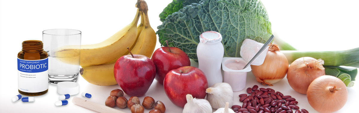 Bananas, apples, onions, yogurt, and various healthy foods along with a bottle of probiotics and a glass of water on a white surface