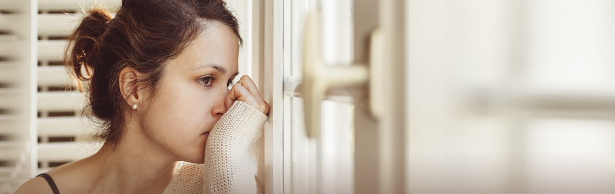 Young woman looks out window with her hand on her face as she contemplates taking anxiety medication