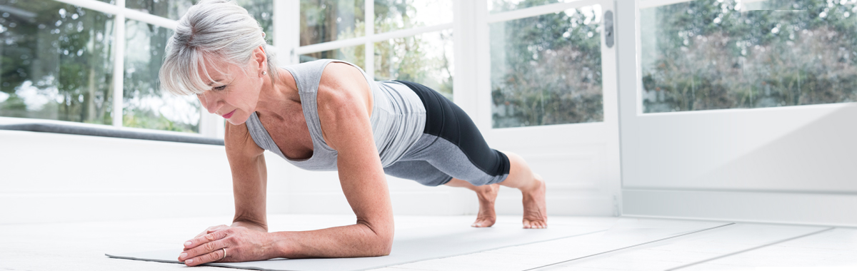 Woman in workout gear doing a plank for muscle activation