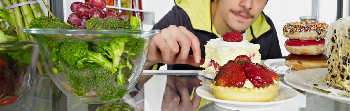 Young man looking at desserts in refrigerator and ignoring vegetables - elimination diet