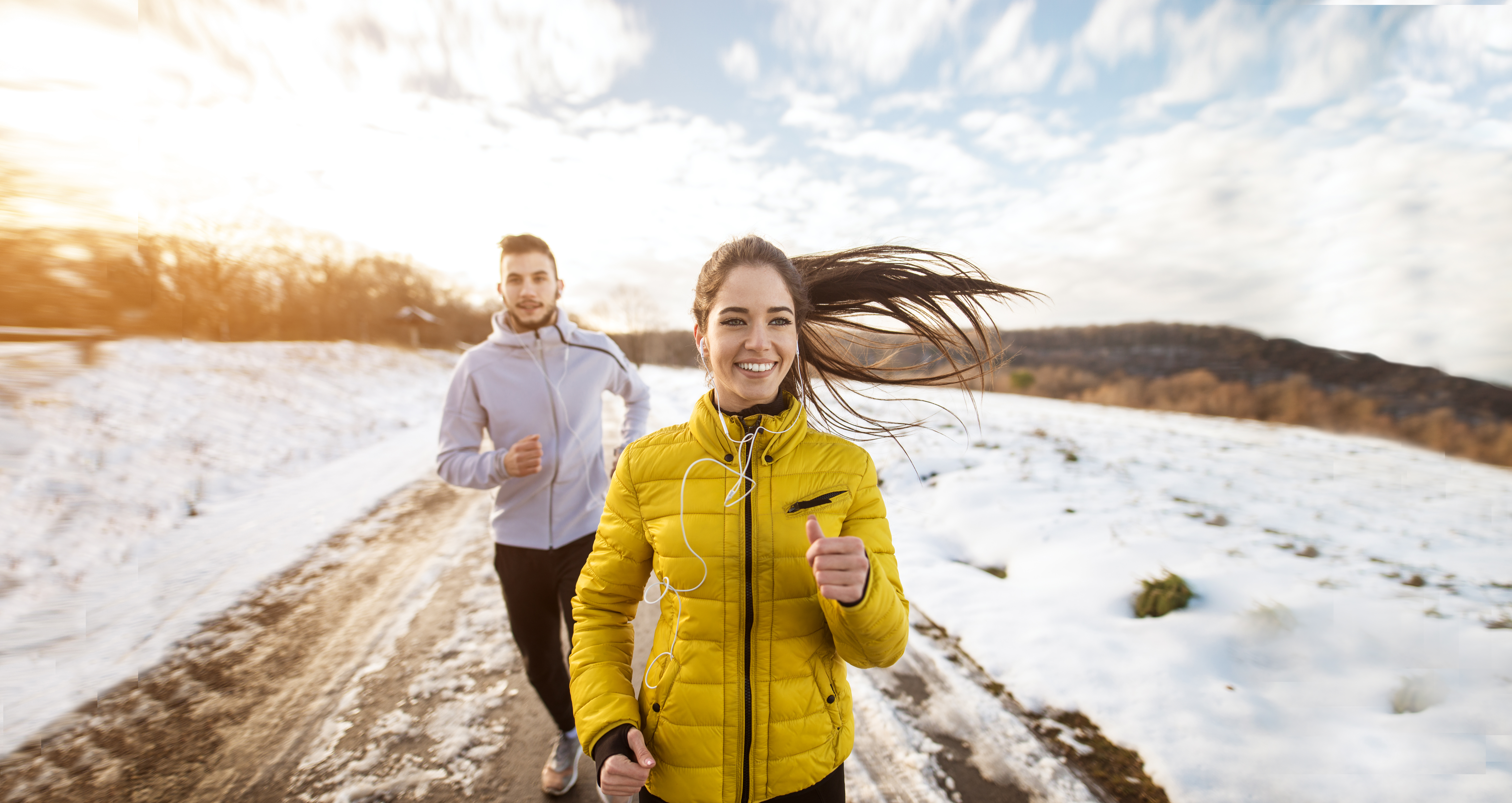 Active athletes sportive couple running with strong persistence on the road in winter nature in the morning.