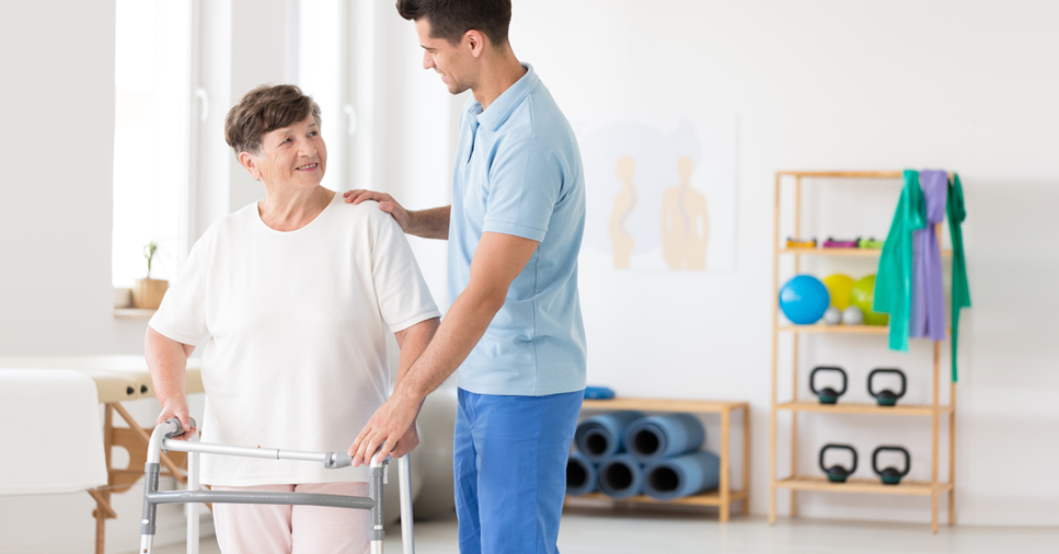 woman with a walker going through rehabilitation for a hip replacement