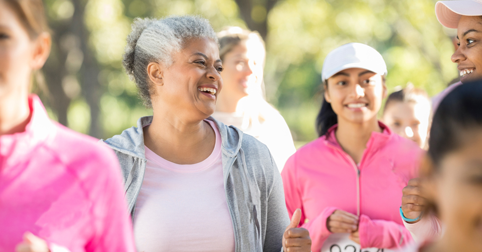 Middle-aged women wearing pink clothing and smiling and laughing while jogging or running in a race