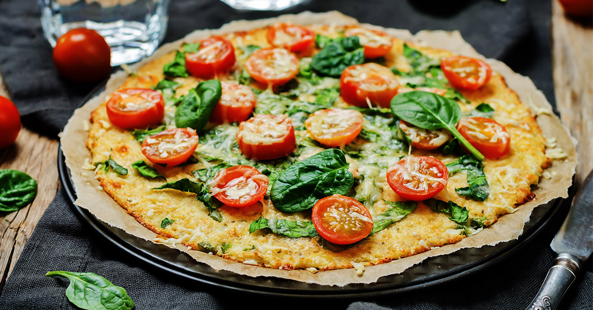Cauliflower Crust Pizza sitting on a table with spinach and tomatoes