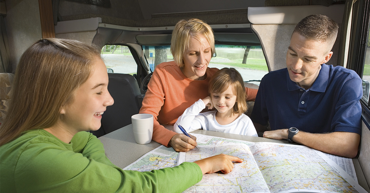 Family of Four looking at a map researching their spring break trip