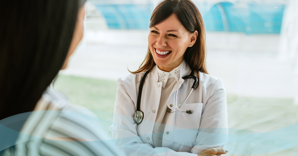 female doctor smiling looking over patient