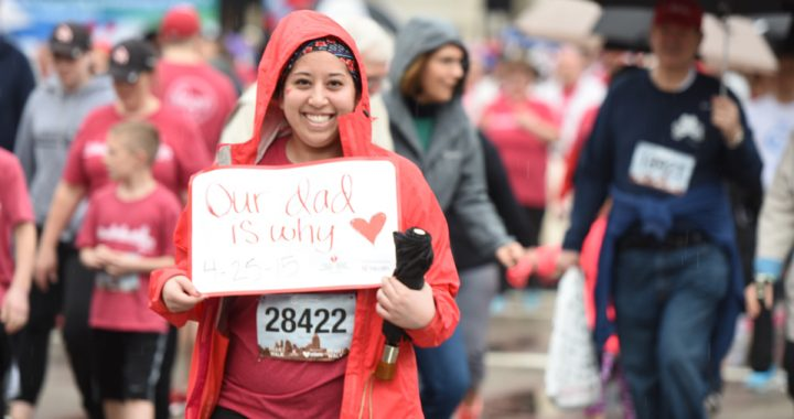 participant of Heart Mini race holding up a sign
