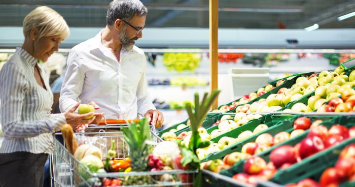 couple looking at produce section of the grocery store