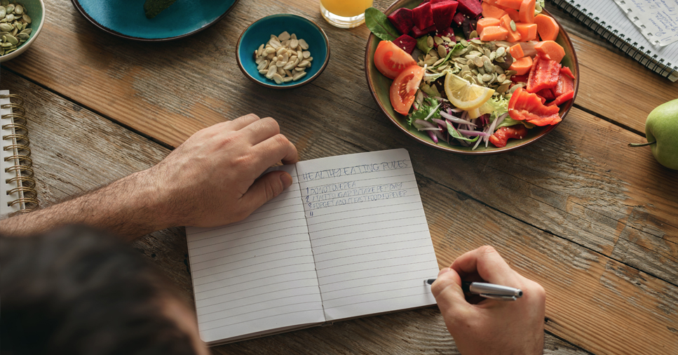 A man writing in a notebook about healthy eating rules for weight loss on a wooden table with a colorful salad in a bowl next to a small bowl of nuts