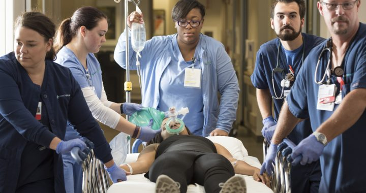 A team of five nurses in blue scrubs attend to a female patient who is unresponsive and laying in a hospital bed