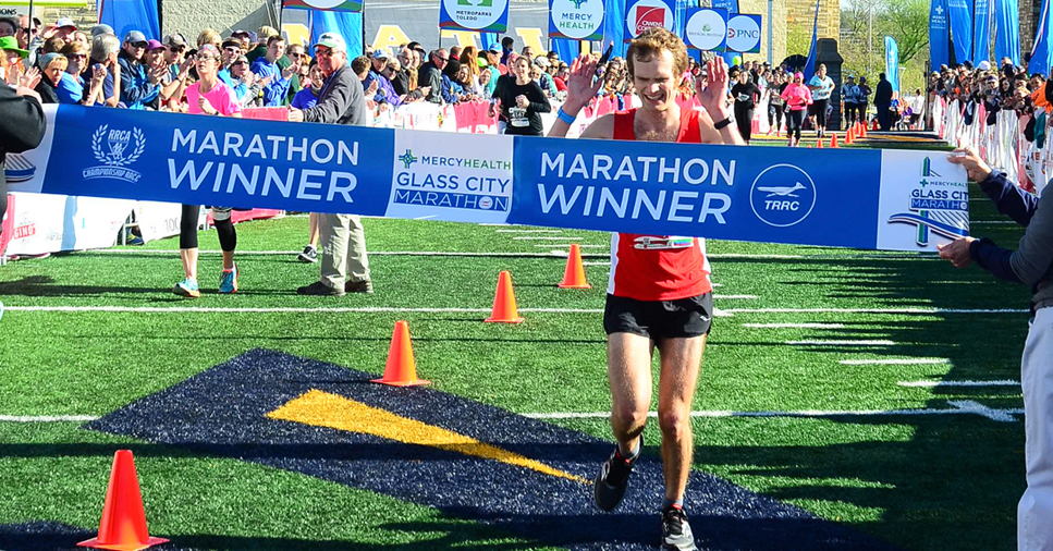 A male runner in a red jersey crosses the Toledo Glass Marathon finish line with his hands in the air and a smile on his face