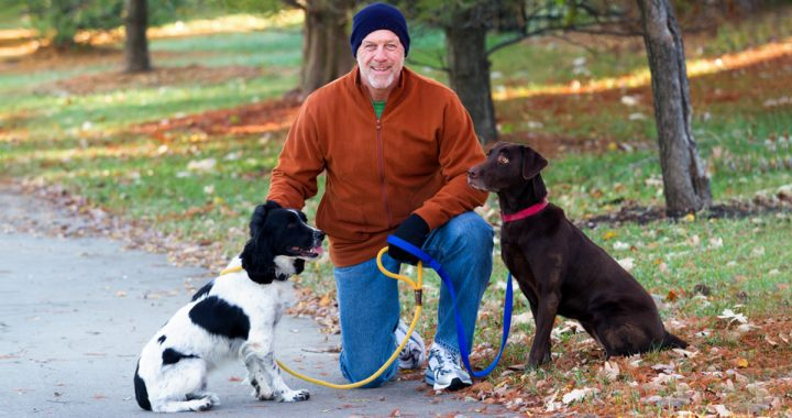 Middle-aged man wearing a brown jacket and jeans kneeling down to pet his two dogs on a fall day. One dog is brown and the other is white with black spots.