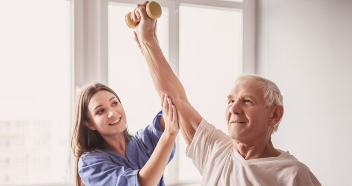 A young female physical therapist helps an older man lift his arm above his head with a small weight in his hand