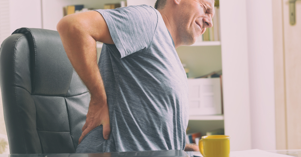 A middle-aged man holds his back in pain as he stands up out of a black office chair with a grimace on his face