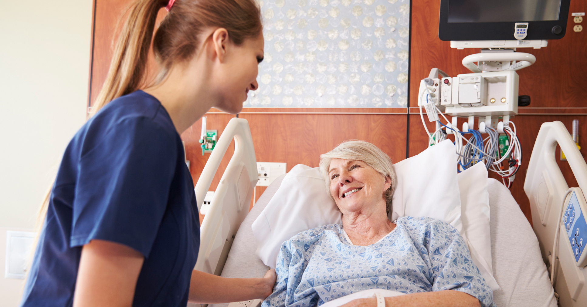 A female nurse in dark blue scrubs tends to an older femail patient in a hospital bed and holds her hand