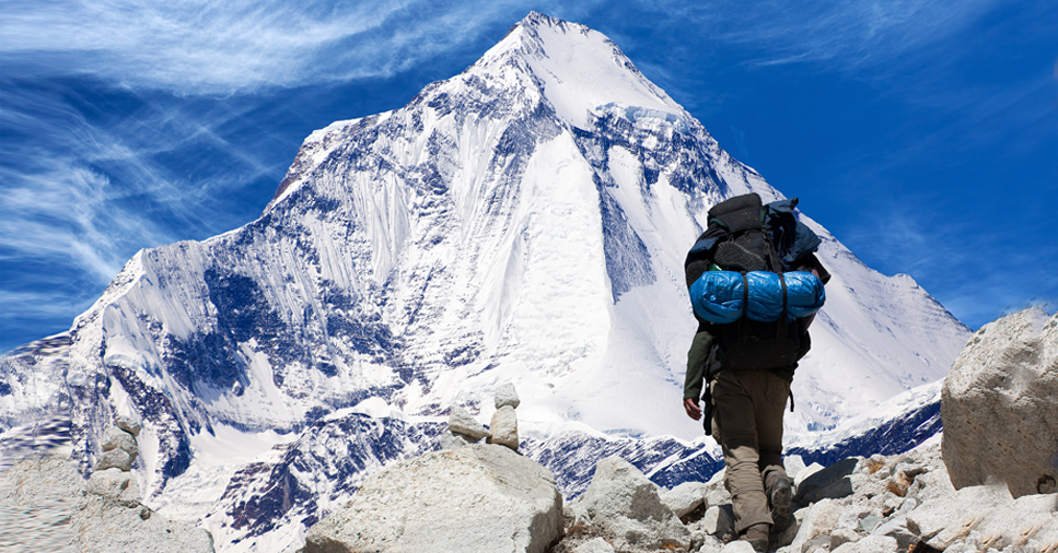 A man with a hiking backpack stands beneath a snow covered mountain