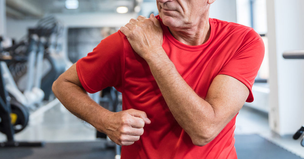 A middle-aged man in a red shirt at the gym clutches his right shoulder with his left hand
