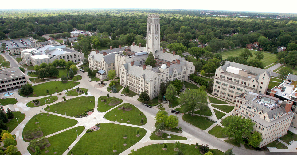 An aerial view of the University of Toledo's campus with green courtyards and old white brick buildings