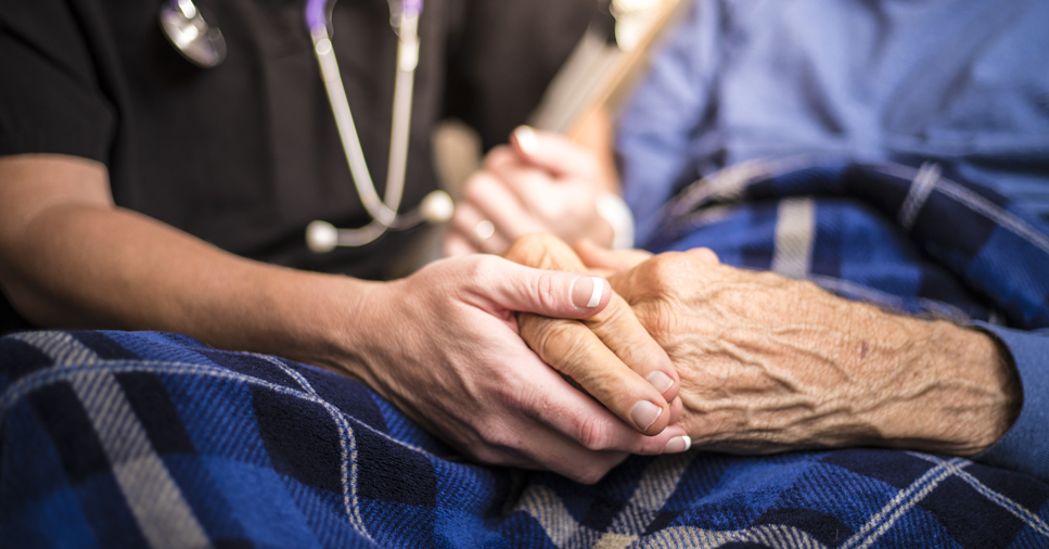 a young nurse's hand holds and elderly person's hand on their lap