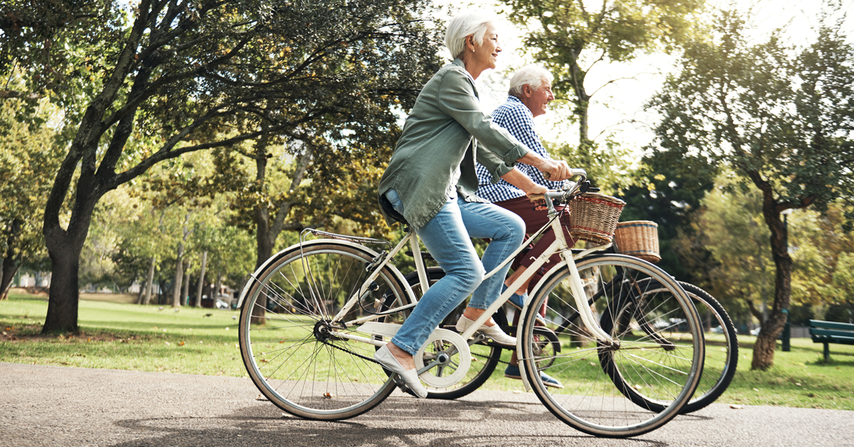An elderly man and woman take a bike ride down a tree covered path