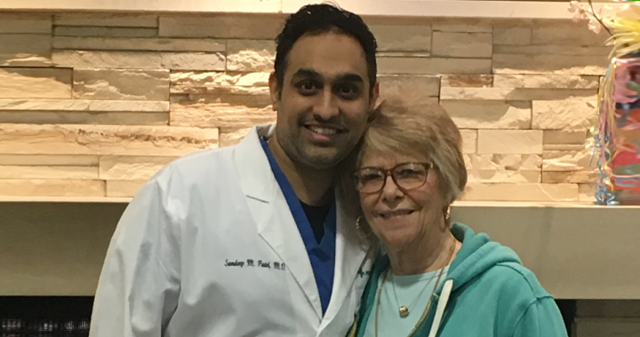 Nancy Paul stands smiling next to Dr. Sandeep Patel who performed her TMVR surgery