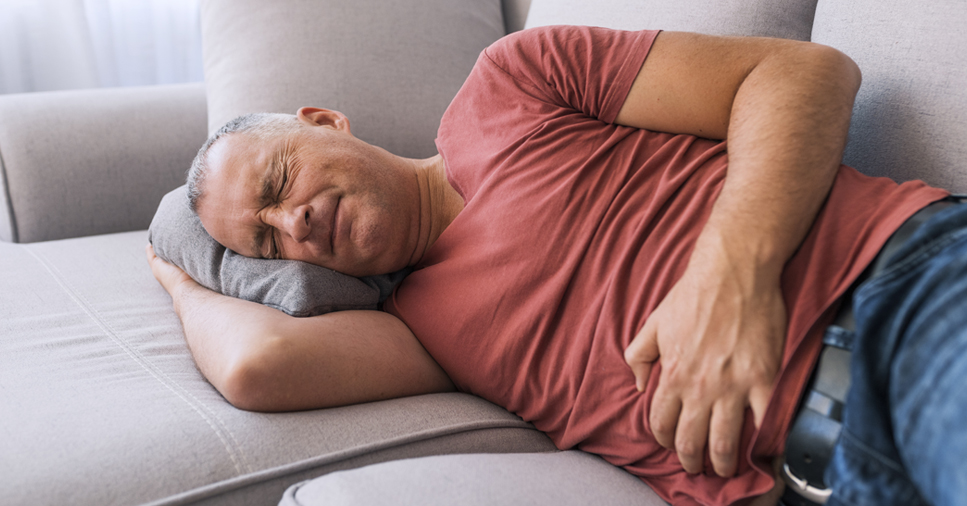 A middle-aged man who has IBS lays on a couch and clutches his stomach in pain
