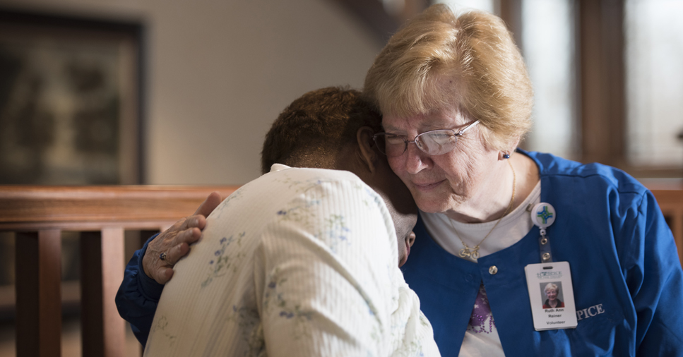 A hospice volunteer holds a patient in a hug